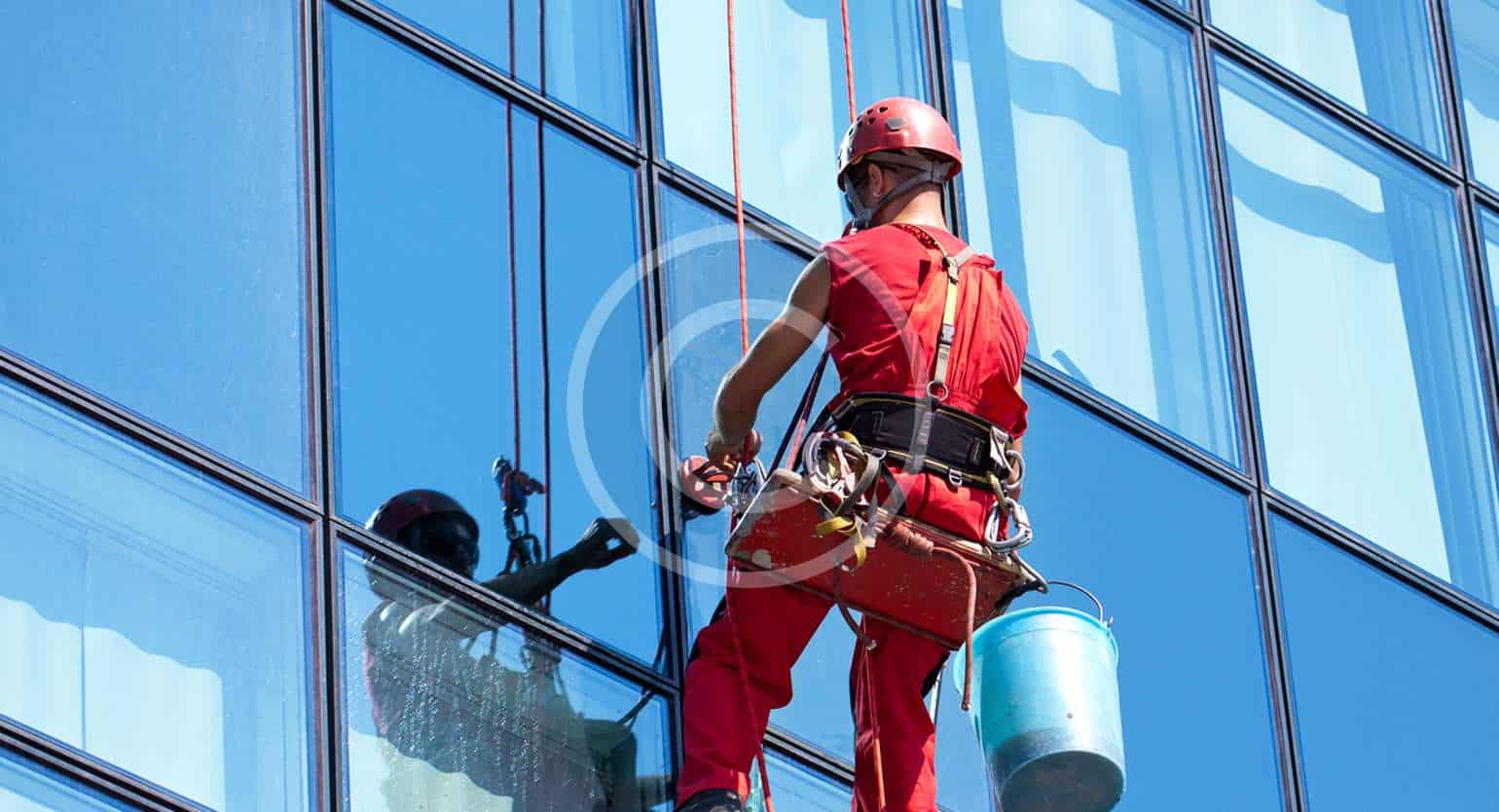 Man cleaning glasses of corporate building in Red Dress