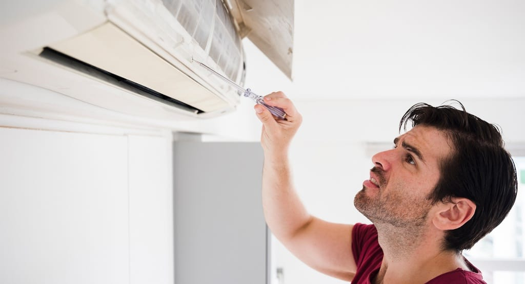 Skilled Technician Inspecting Air Conditioner